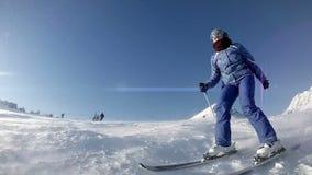 El salpicar femenino del esquiador va al lado del vídeo de la cámara lenta de la cámara almacen de video