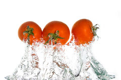 el saltar de 3 tomates del agua Imagenes de archivo