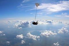 El saltar en caída libre en tándem en el cielo asombroso nublado foto de archivo libre de regalías