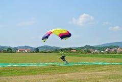 El saltar en caída libre y aterrizaje del Skydiver con el paracaídas amarillo de la rosa púrpura colorida en la taza que se lanza imagen de archivo libre de regalías