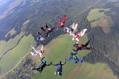 El saltar en ca?da libre de la formaci?n Los Skydivers han hecho un c?rculo en el cielo imágenes de archivo libres de regalías