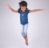 El salto de la muchacha feliz y la mirada abajo Imagen de archivo