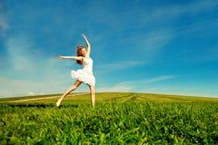 El salto de la mujer Muchacha hermosa joven que salta en campo en el gra Fotos de archivo libres de regalías