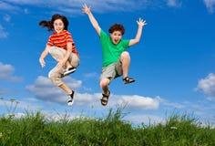El salto de los cabritos al aire libre Fotos de archivo libres de regalías