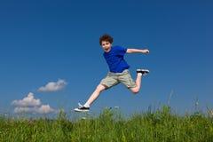 El salto del muchacho al aire libre Foto de archivo