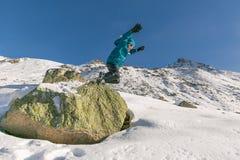 El salto del muchacho de una roca en nieve Imagen de archivo libre de regalías