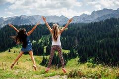 El salto feliz de dos muchachas en montañas apoya la visión Fotografía de archivo