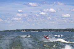El salto personal del Watercraft tres despierta en un lago con los árboles y las casas en línea de la playa en la distancia debaj Foto de archivo