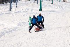 El salvador del esquí está llevando una cuna vacía abajo de la montaña concepto de patinaje peligroso, freeride, esquiador herido imagenes de archivo