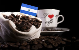 El Salvador flag in a bag with coffee beans isolated on black. Background royalty free stock image