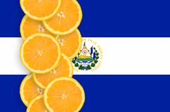 El Salvador flag and citrus fruit slices vertical row. El Salvador flag and vertical row of orange citrus fruit slices. Concept of growing as well as import and stock photo