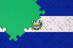 El Salvador flag is depicted on a completed jigsaw puzzle with free green copy space on the left side.  stock image