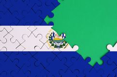 El Salvador flag is depicted on a completed jigsaw puzzle with free green copy space on the right side.  stock photo