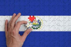 El Salvador flag is depicted on a puzzle, which the man`s hand completes to fold.  royalty free stock image