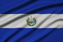 El Salvador flag is depicted on a sports cloth fabric with many folds. Sport team banner. El Salvador flag is depicted on a sports cloth fabric with many folds stock photo