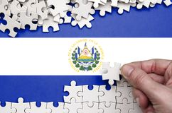El Salvador flag is depicted on a table on which the human hand folds a puzzle of white color.  stock photos