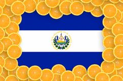 El Salvador flag in fresh citrus fruit slices frame. El Salvador flag in frame of orange citrus fruit slices. Concept of growing as well as import and export of stock illustration