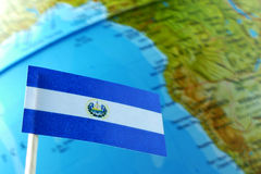 El Salvador flag with a globe map as a background. Macro royalty free stock image