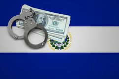 El Salvador flag with handcuffs and a bundle of dollars. The concept of breaking the law and thieves crimes.  royalty free stock image