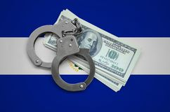 El Salvador flag with handcuffs and a bundle of dollars. Currency corruption in the country. Financial crimes.  royalty free stock photography