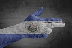 El Salvador flag painted on male hand like a gun. On concrete background royalty free stock image