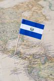 El Salvador flag pin on a world map. Paper flag pin of El Salvador on a world map showing neighboring countries. Officially the Republic of El Salvador, it is royalty free stock photos