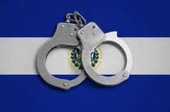 El Salvador flag and police handcuffs. The concept of observance of the law in the country and protection from crime.  royalty free stock image