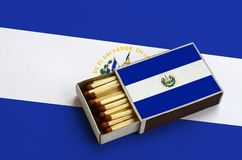 El Salvador flag is shown in an open matchbox, which is filled with matches and lies on a large flag.  royalty free stock photos