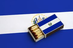 El Salvador flag is shown in an open matchbox, which is filled with matches and lies on a large flag.  stock photo