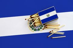 El Salvador flag is shown on an open matchbox, from which several matches fall and lies on a large flag.  stock image