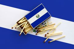 El Salvador flag is shown on an open matchbox, from which several matches fall and lies on a large flag.  royalty free stock images