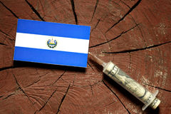 El Salvador flag on a stump with syringe injecting money. In flag stock photo