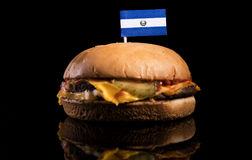 El Salvador flag on top of hamburger isolated on black. Background royalty free stock photos