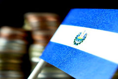 El Salvador flag waving with stack of money coins. Macro stock photos