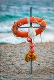 El salvavidas de la seguridad con el casquillo de la cuerda y de los childs puso la cruz contra fondo de la resaca del mar Pase l imagen de archivo