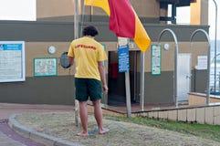 El salvavidas que aumenta la bandera en la estación de socorro de bronce de la resaca de la playa en Umhlanga oscila Imagenes de archivo
