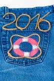 El salvavidas y la cuerda numeran 2016 en fondo del bolsillo de los vaqueros entonado Fotografía de archivo