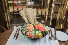 El sashimi del sushi y los rollos de sushi determinados sirvieron en la pizarra de piedra Foto de archivo libre de regalías