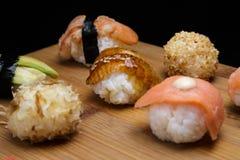 El sashimi y los rollos determinados del sushi sirvieron en el escritorio de madera Imagen de archivo