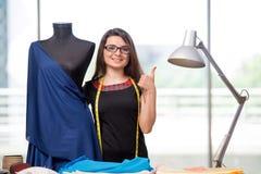 El sastre de la mujer que trabaja en la nueva ropa Imagen de archivo libre de regalías
