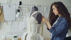 El sastre de sexo femenino joven está ajustando la ropa en la adaptación del maniquí con los pernos de costura y la medición con  almacen de metraje de vídeo