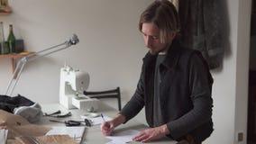 El sastre de sexo masculino dibuja el bosquejo creativo de la ropa en taller metrajes