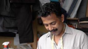 El sastre hindú con centímetro del cuello cose la camisa en un taller en la ciudad vieja de Dubai almacen de video