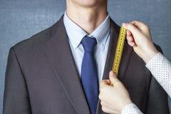 El sastre mide el traje con un primer de la cinta métrica fotos de archivo
