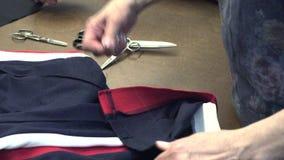 El sastre rasga la ropa con sus manos almacen de metraje de vídeo