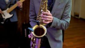 El saxofón, instrumento de música jugó por el músico del jugador del saxofonista en banquete de boda metrajes