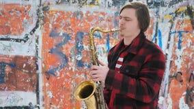 El saxofonista toca el saxofón, en invierno almacen de video