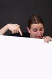 El señalar adolescente en la muestra en blanco Foto de archivo