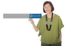El señalar asiático mayor de la mujer aislado en el fondo blanco con el SE Imagen de archivo