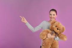 El señalar del adolescente. Adolescente feliz que sostiene un oso de peluche a Imagen de archivo